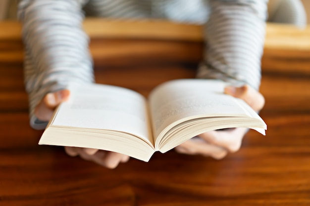 Hand holding a book at home Premium Photo