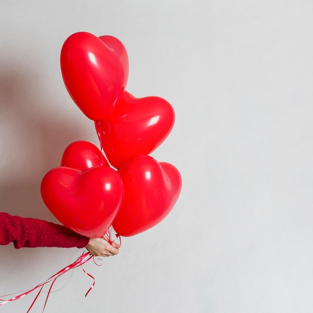 Hand holding a bunch of balloons Free Photo