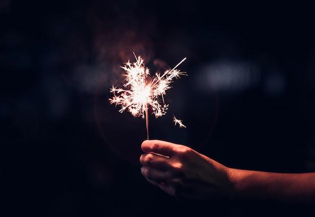 Hand holding burning sparkler blast on a black background Premium Photo