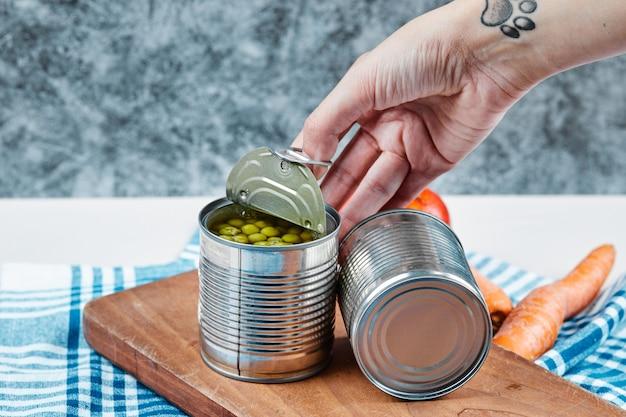 Mano che tiene una lattina di piselli bolliti su un tavolo bianco con verdure e tovaglia. Foto Gratuite
