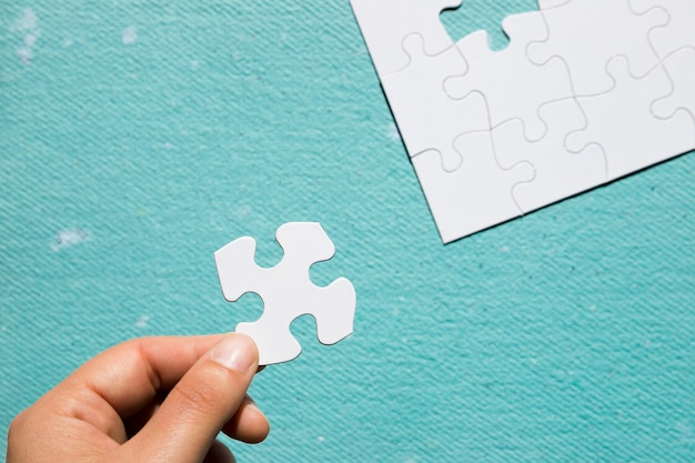 Hand holding cardboard white jigsaw puzzle over blue textured backdrop Free Photo