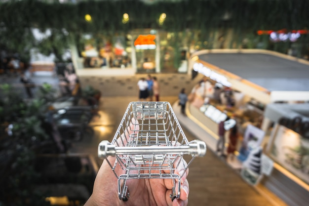 A hand holding cart model with blur indoor shopping . Premium Photo