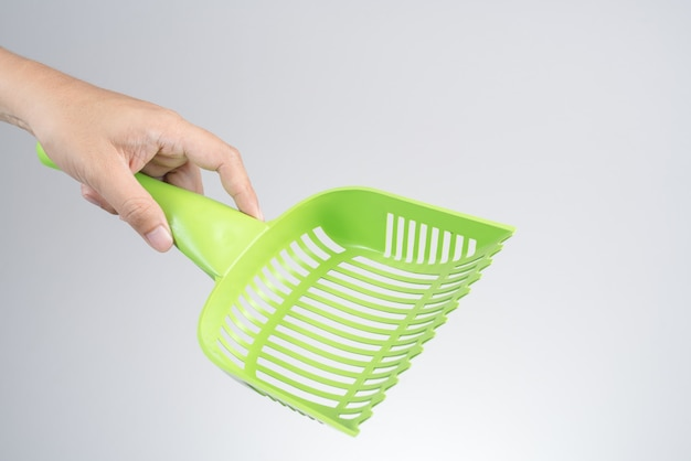 Hand holding cat or pet plastic litter tray scoop or waste scooper Premium Photo