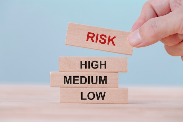 Hand holding chooses wooden block cubes with risk word. risk management concept. Premium Photo