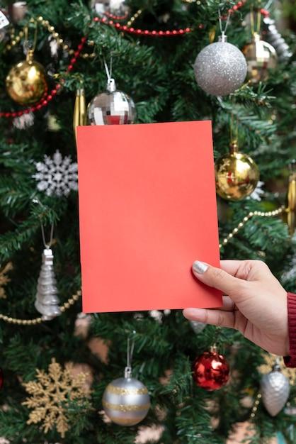 Hand holding christmas holiday greeting design mockup card on christmas tree background. Premium Photo