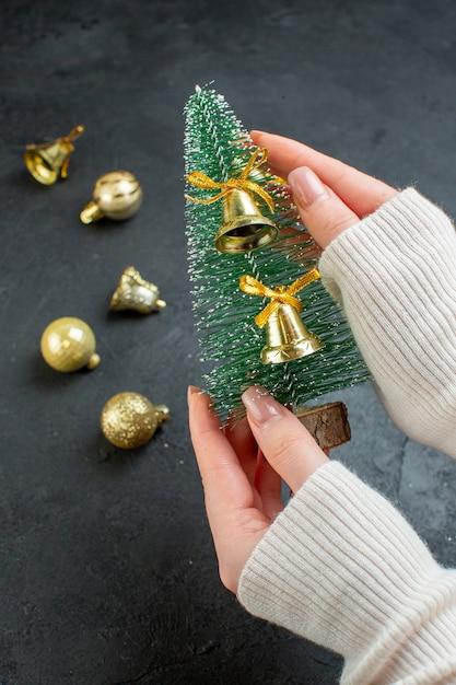 어두운 배경에 크리스마스 트리와 장식 액세서리를 들고 손 무료 사진
