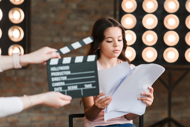 Hand holding clapper board in front of girl reading scripts in studio Premium Photo