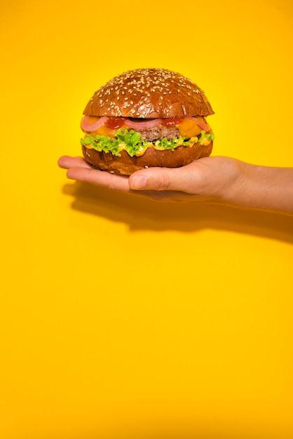 Hand holding classic beef burger with lettuce Free Photo