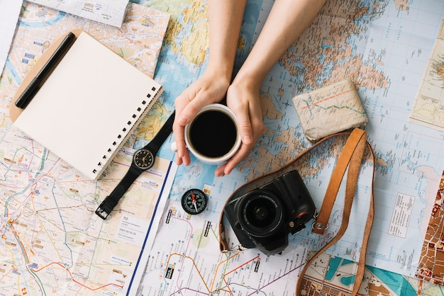 Hand holding coffee cup on map surrounded with spiral notepad; compass; wristwatch; camera and strap Free Photo