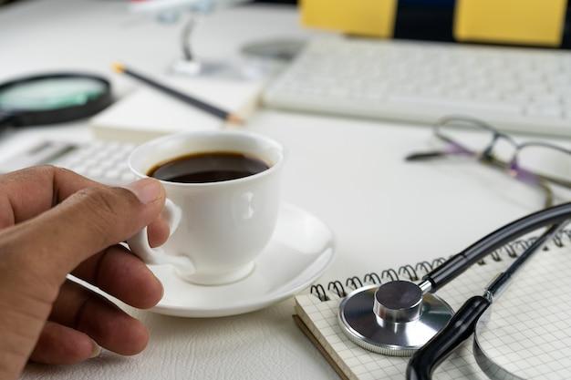 白い革製のテーブルのビジネスオブジェクトとコーヒーカップを持っている手。 Premium写真