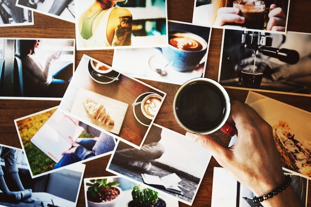 Hand holding coffee cup with may photograph on the table Free Photo