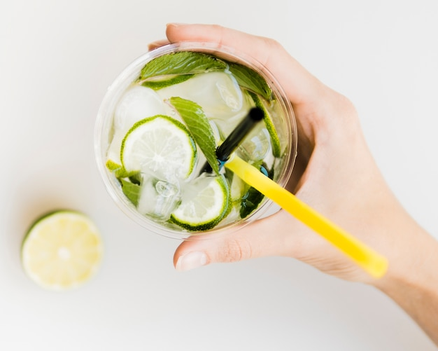 Hand holding cold cocktail with mint, lime and ice Free Photo