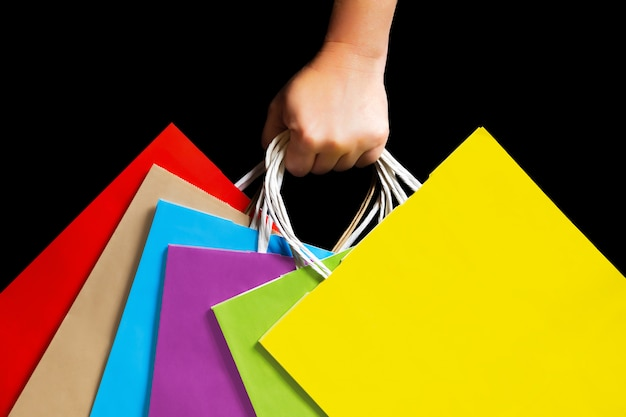 Hand holding colorful paper bags. Premium Photo