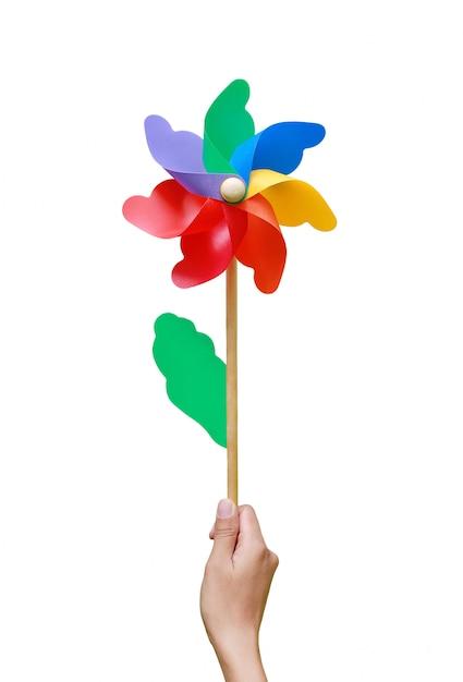 Hand holding colorful pinwheel over white background Premium Photo