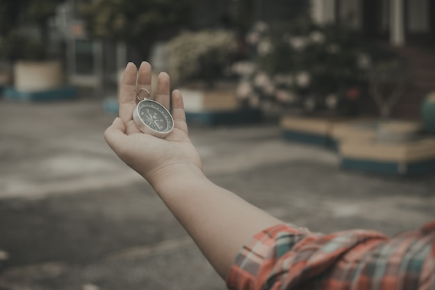 Hand holding a compass for finding travel destinations. vintage style. Premium Photo