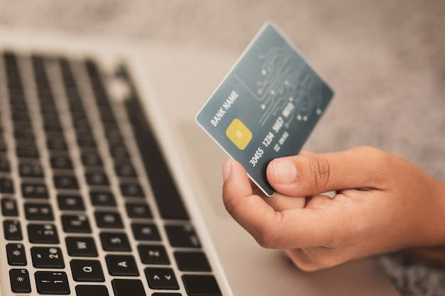 Hand holding a credit card next to a laptop Free Photo