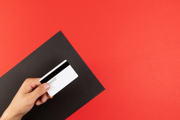 Hand holding a credit card on red background Free Photo