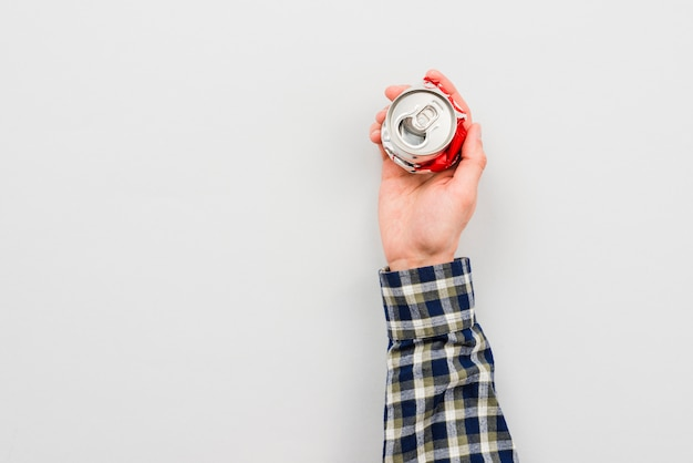 Hand holding crumpled can of drink Free Photo