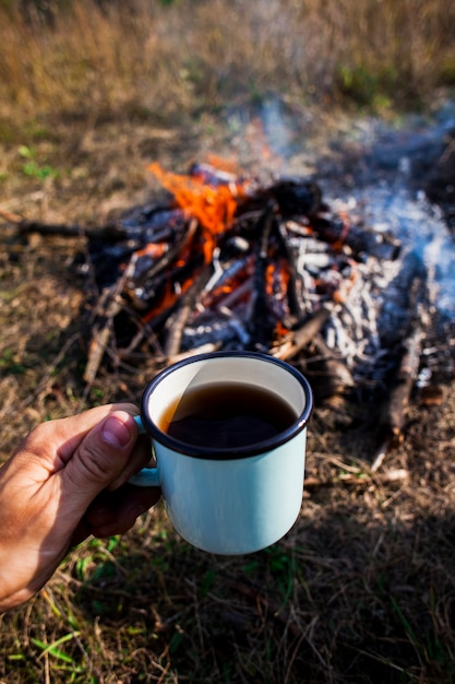 Hand holding a cup of coffee next to a campfire Free Photo