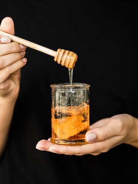 Hand holding delicious honey jar Free Photo