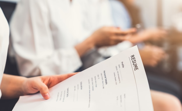 Hand holding document and submit resume to employer to review job application Premium Photo