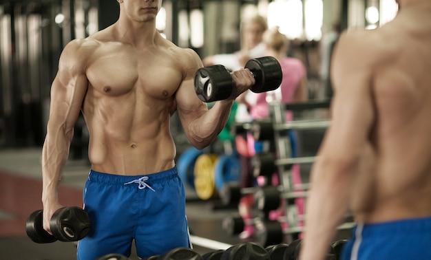 ダンベルを持っている手。クローズアップ。ジムで筋肉の腕。トレーニング、スポーツ、手、ダンベル、トレーニング。 -健康的なライフスタイルとフィットネスのコンセプト。フィットネスとスポーツに関する記事。 Premium写真