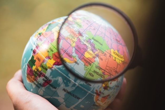 Hand holding earth globe and magnifying glass above the middle east. Premium Photo