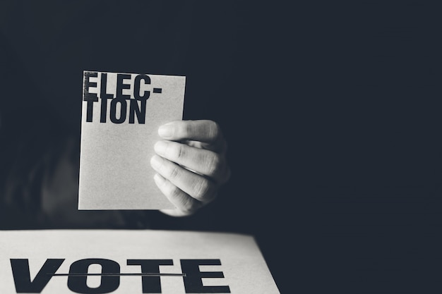 Hand holding election card and vote box, democracy concept, black and white tone Premium Photo
