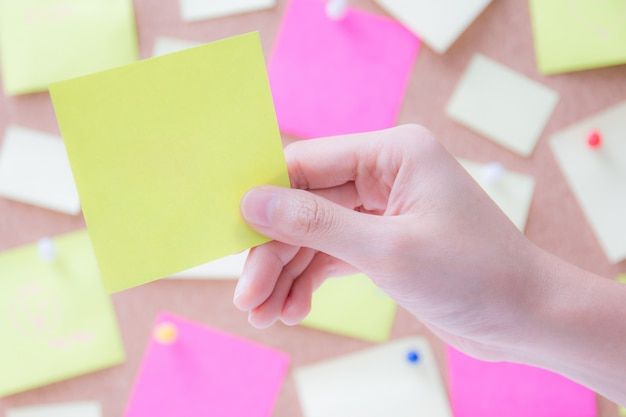 Hand holding empty post it paper or sticky note with blurred cork board background for insert your messages. Premium Photo