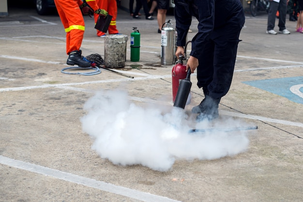 Hand holding fire extinguisher and spraying to the burning fire Premium Photo