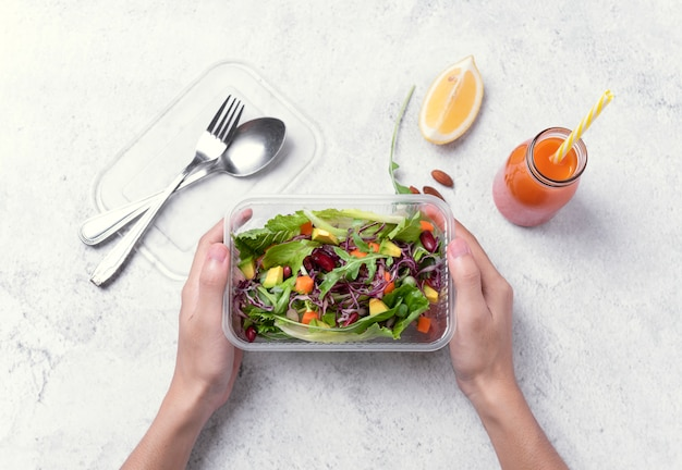 Hand holding fresh healthy diet lunch box with vegetable salad on table background. Premium Photo