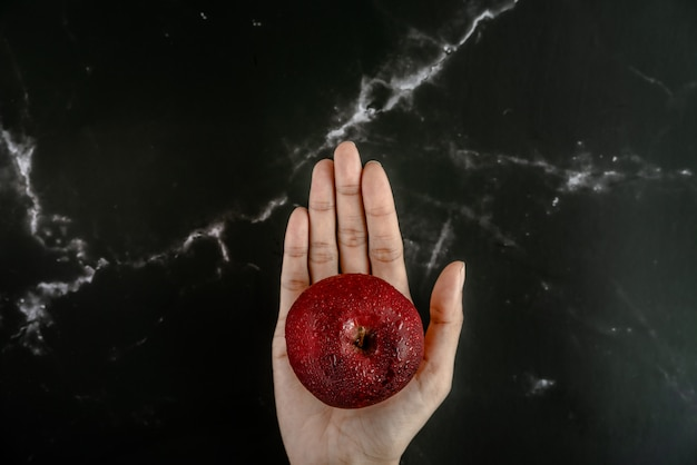 Hand holding fresh red apple with water spray droplets on apple over a black marble surface. top view flat lay composition. Premium Photo