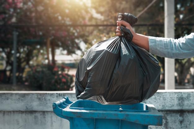 Hand holding garbage black bag putting in to trash Premium Photo