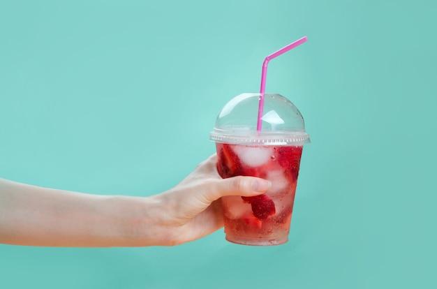 분홍색과 녹색 배경에 딸기 칵테일의 유리를 잡고 손 프리미엄 사진