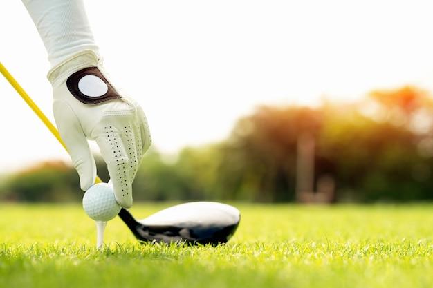 코스, 티 오프, 오른쪽에 복사 공간에 티와 골프 공을 들고 손 프리미엄 사진