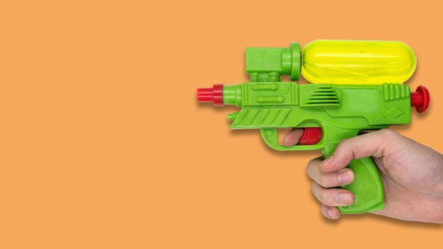 Hand holding gun water toy on orange background. free space for text Premium Photo