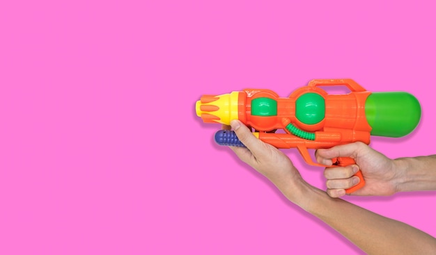 Hand holding gun water toy on pink background. free space for text Premium Photo