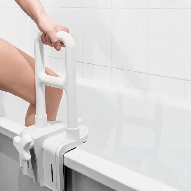 Hand holding the handrail in the bathroom Premium Photo