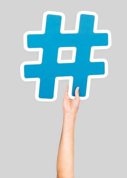 Hand holding hashtag symbol Free Photo