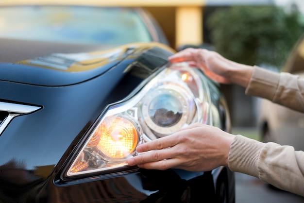 Hand holding headlight of darkcar Free Photo