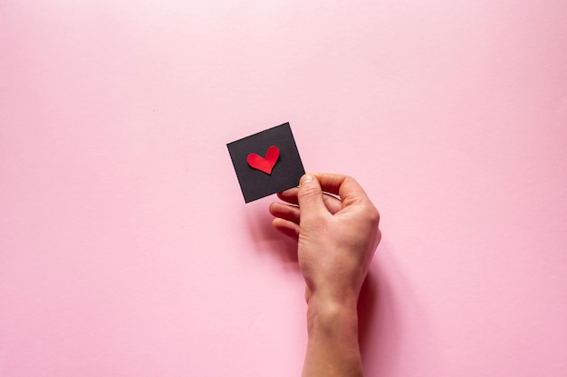 The hand  holding a heart  over pink wall, valentine's day. flat lay Premium Photo