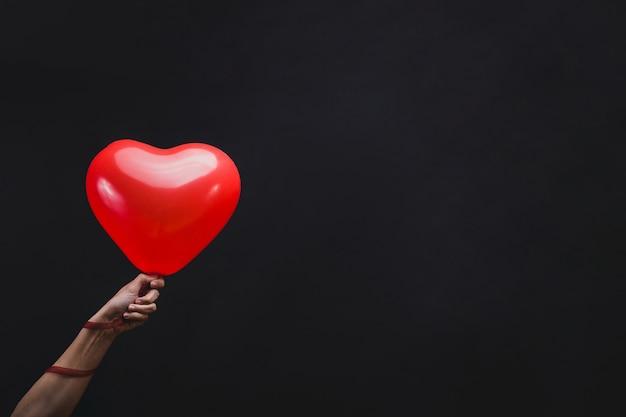 Hand holding a heart shaped balloon Free Photo