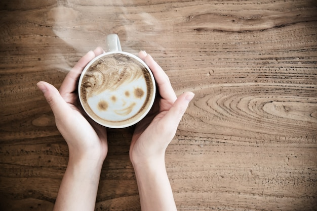 Hand holding hot coffee cup - people with coffee concept Free Photo