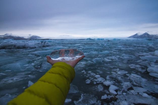 背景にアイスランドの曇り空の下で凍った海と氷を持っている手 無料写真