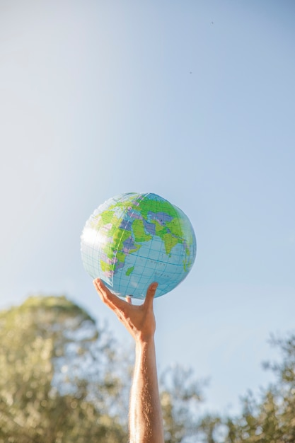 Hand holding inflatable planet model Free Photo