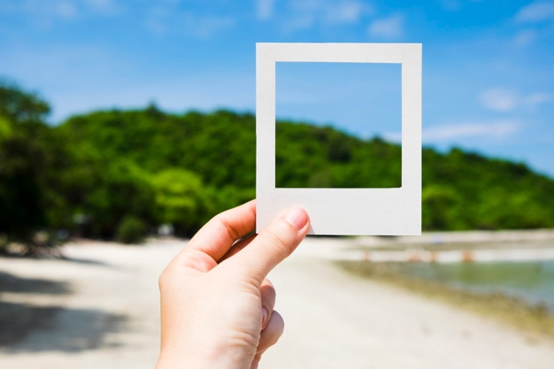 Hand holding instant photo frame at beach Free Photo