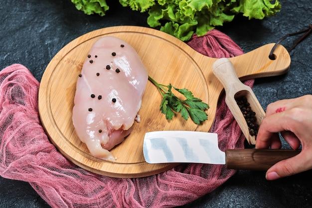 Рука держит нож и кусок сырого куриного филе на деревянной тарелке со свежими овощами и скатертью. Бесплатные Фотографии