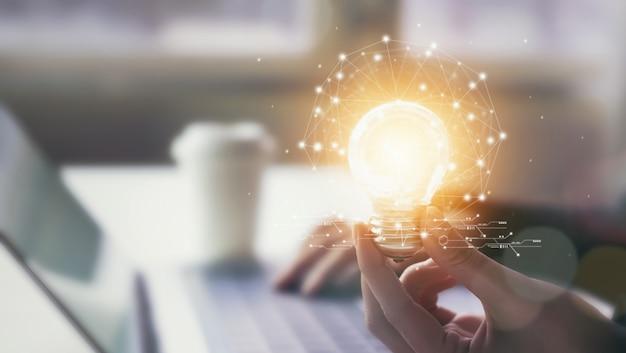 Рука, держащая лампочку с новаторством и креативностью, является ключом к успеху. Premium Фотографии