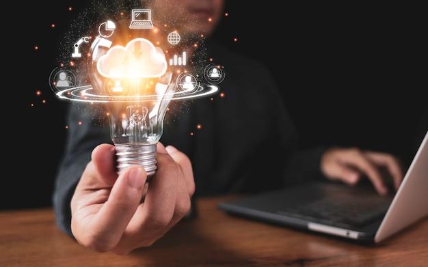 Вручите держать лампочку с облачными вычислениями и значками технологии такими как диаграмма портативного компьютера. облачные технологии управления большими данными включают бизнес-стратегию Premium Фотографии