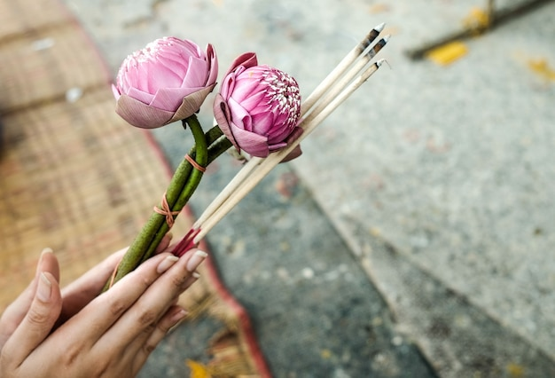Hand Holding Lotus Flower Candle And Incense Sticks To Pay Respect